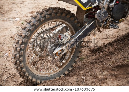 Rear wheel of sport bike. Dirty road, motocross theme - stock photo