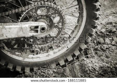 Rear wheel of sport bike on dirty motocross road - stock photo