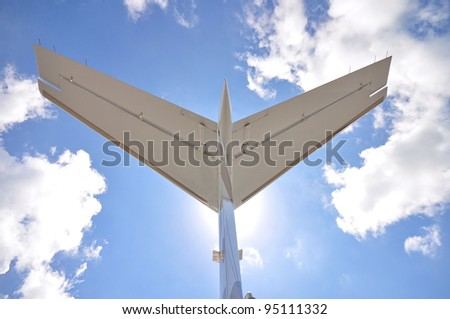 Rear wing of aircraft against blue sky - stock photo