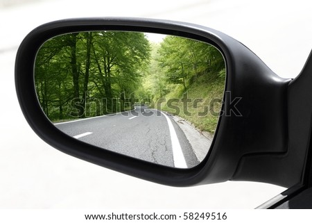 rearview car driving mirror view green forest road [Photo Illustration] - stock photo