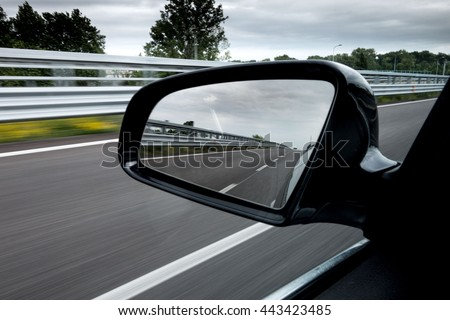 Rearview mirror of a car traveling on a highway