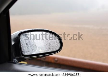 Rearview mirror - rain - stock photo