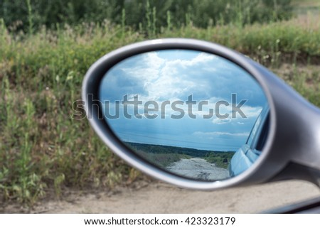 Rearview mirror with blue sky behind. - stock photo