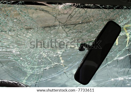 Rearview mirror with shattered windshield - stock photo