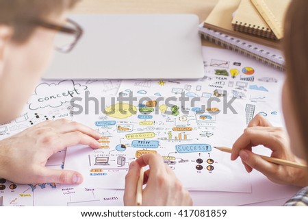 Rearview of businesspeople discussing business sketches on desktop with closed laptop and spiral notepads - stock photo