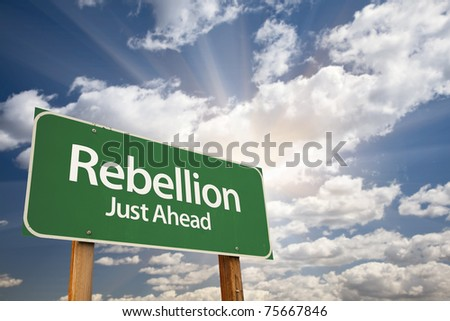 Rebellion Green Road Sign with Dramatic Clouds, Sun Rays and Sky.