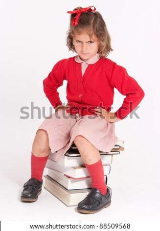 Rebellious little schoolgirl sitting on a pile of books - stock photo