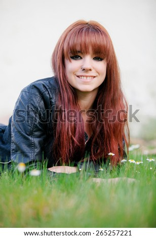 Rebellious teenager girl with red hair lying on the grass - stock photo