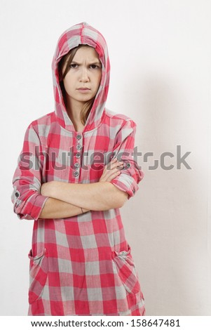 Rebellious teenager with arms across  - stock photo