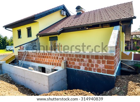 Rebuilding a family house and adding an extension. Setting up a construction site with formwork. Digging the brick foundation for hydro isolation of basement. - stock photo