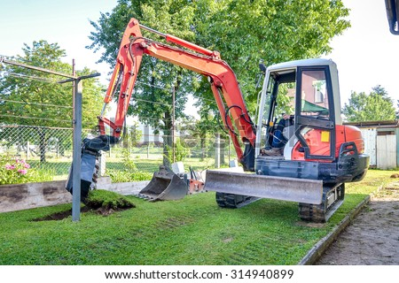 Rebuilding a house and digging dirt with excavator. Digger is starting to excavate the lawn. - stock photo