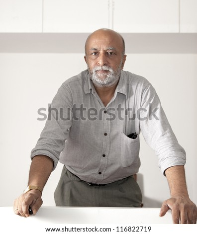 receding indian man, beard and western dress looking straight into the camera, holding a remote switch and having sunglasses in his rolled up long sleeve shirt, Stern firm straight facial expression - stock photo