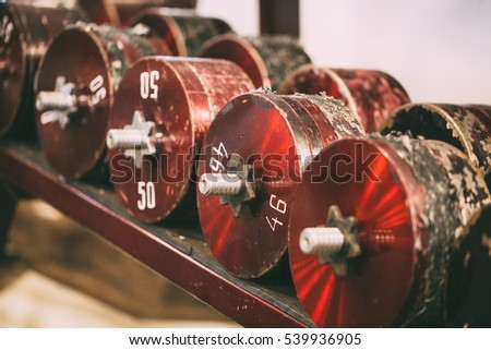 Receding row of weights lined up in a gym waiting for clients