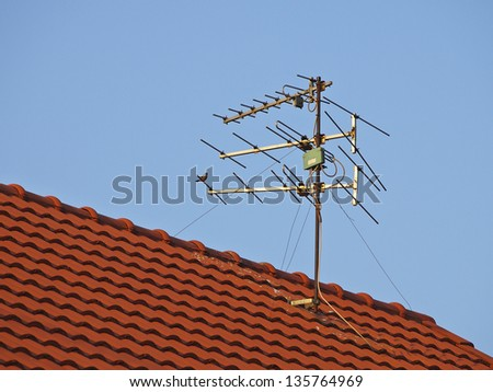 receiver antenna on red roof in sunlight - stock photo