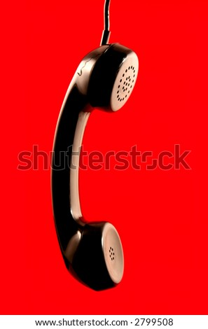 Receiver of a 1960's corded telephone, hanging down, with red background. - stock photo