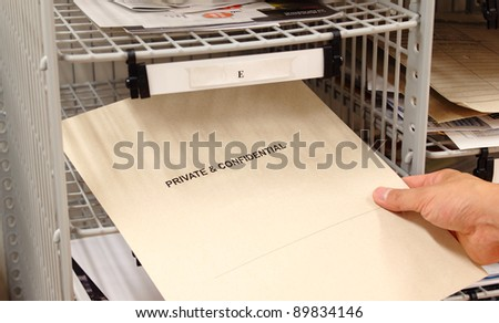Receiving a private and confidential envelope in the office mailroom. - stock photo