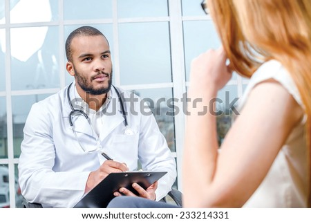 Receiving physician. Confident and smiling doctor listens to the patient's problems in his office. People sit on top of each other. The doctor writes the history of into a tablet - stock photo