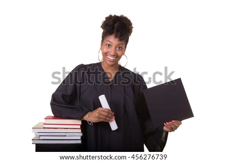 Recent college graduate in a cap and gown next to a stack of books isolated on white - stock photo