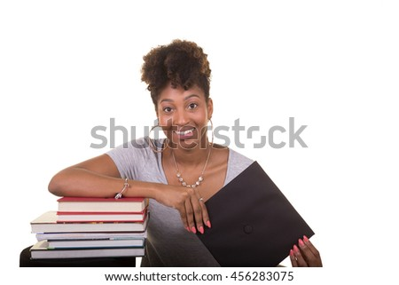 Recent college graduate next to a stack of books - stock photo