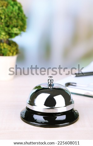 Reception bell on desk, on bright background - stock photo