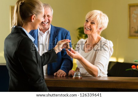 Reception - Guests check in at hotel and getting the key - stock photo