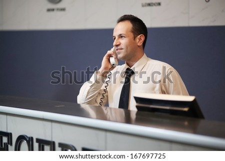 Reception of hotel, desk clerk, man taking a call and smiling .Night light. - stock photo