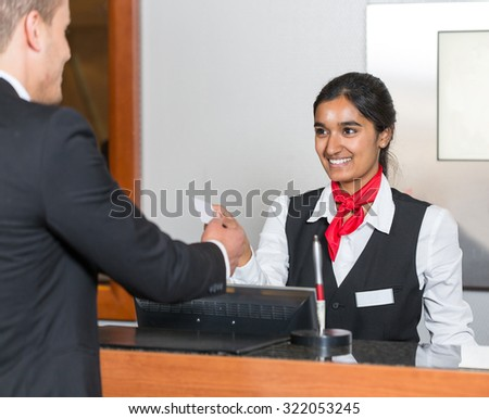 receptionist at hotel reception handing key card to guest or client - stock photo