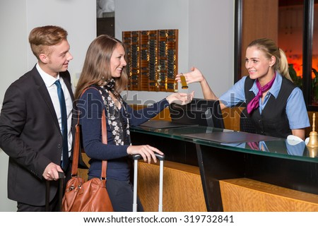 receptionist at hotel reception handing over a key to guest or customer - stock photo