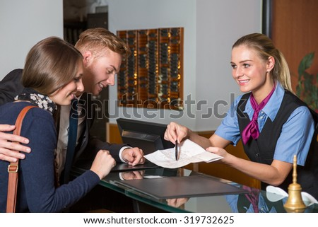 receptionist at hotel showing guest something on a map - stock photo