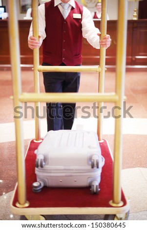 Receptionist in red vest carries suitcase of guest on special cart. - stock photo