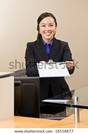 Receptionist offering clipboard and pen at front desk - stock photo