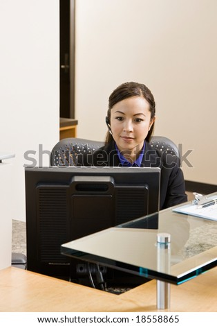 Receptionist with telephone earpiece working at desk in office - stock photo