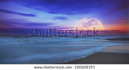 Recessing tide and moonrise over sandy ocean beach - stock photo