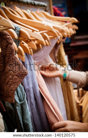 Recession bargains: rack of second-hand dresses for sale at market. Portrait orientation. - stock photo