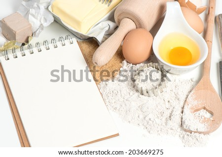 recipe book and baking ingredients eggs, flour, sugar, butter, yeast. food background - stock photo