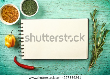 Recipe book and spices on blue wooden background - stock photo
