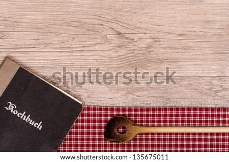 Recipe book and wooden spoon on a checkered table cloth - stock photo