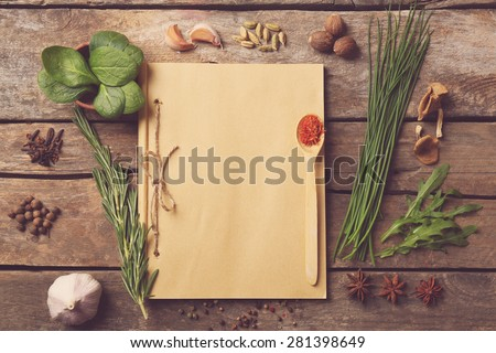 Recipe book page with different herbs on wooden background - stock photo