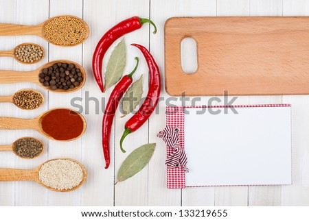 Recipe book, spices in wooden spoons, plank on white wood background - stock photo