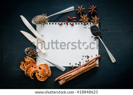 recipe book with fresh herbs and spices on wooden background - stock photo