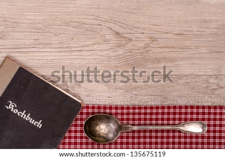 Recipe book with old silver spoon on a checkered cloth and wooden board - stock photo