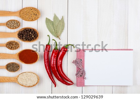 Recipe cook book, chili, spices on white wood background