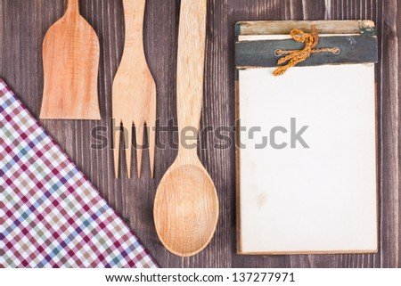 Recipe cook book, kitchen tablecloth, wooden spoon, fork on wood textured background - stock photo
