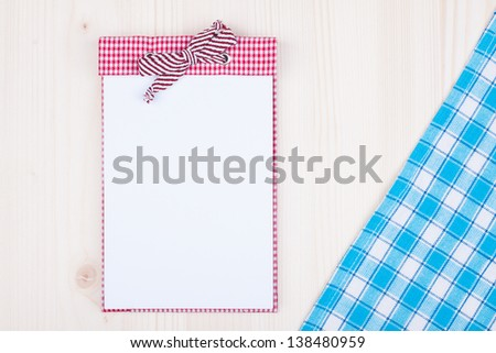 Recipe cook note book, tablecloth on white wood background - stock photo