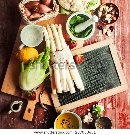 Recipe ingredients for a healthy vegetarian meal with fresh asparagus tips, cauliflower, kohlrabi, nuts, raisins, garlic, shallots, olive oil, herbs and spices on a blank school slate, overhead view - stock photo