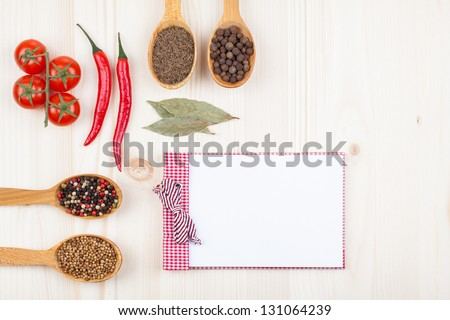 Recipe notebook, chili, cherry tomatoes, spices on white wood background