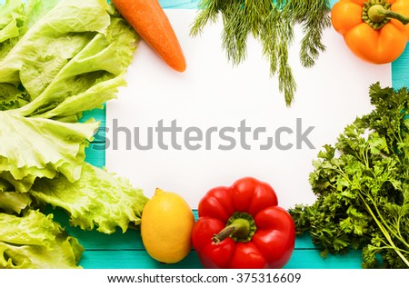 Recipe paper with copy space and vegetables on the kitchen table. Top view