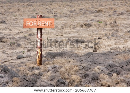 reclamation land area with wooden sign pole for rent  - stock photo
