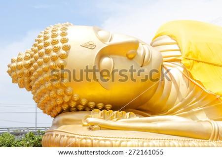 Reclining Buddha gold statue face - stock photo