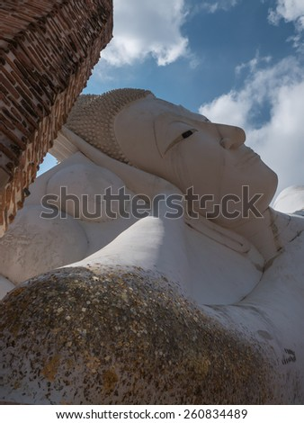 Reclining Buddha in ancient Buddhist temple in Thailand - stock photo